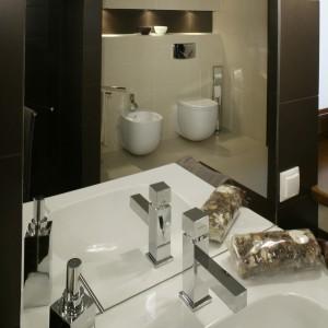 W eleganckiej łazience ważne są starannie dobrane akcesoria oraz szczegóły wykończeniowe. Ogromne lustro sięga od sufitu do krawędzi umywalek. Fot. Monika Filipiuk.