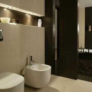 Jasny kolor płytek na podłodze oraz ciemna półścianka wyznaczają granicę między higieniczną i relaksującą częścią łazienki. Podświetlona wnęka nad sedesem i bidetem jest miejscem na drobiazgi i ozdobą. Fot. Monika Filipiuk.