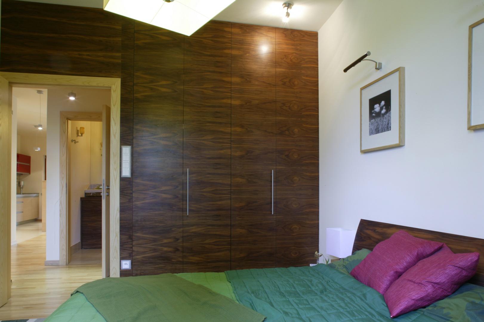 Dominujący w łazience fornir orzecha amerykańskiego, obecny jest te w sypialni  na drzwiach garderoby, szafkach nocnych i łóżku. Fot. Bartosz Jarosz.