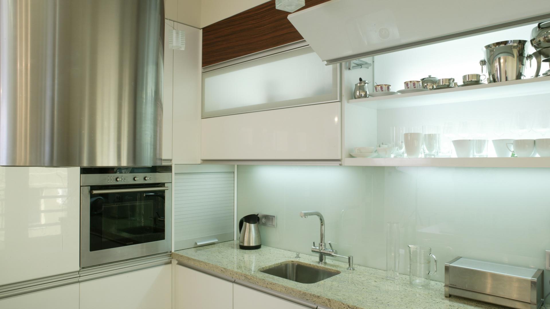 Białe fronty na wysoki połysk, szkło i granit, cieplejszym akcentem jest jedynie fornir z palisandru. Półki w górnych szafkach są podświetlone. Fot. Monika Filipuk.