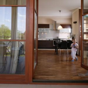 """Po uchyleniu dwuskrzydłowych drzwi na taras apartament zyskuje dodatkową, """"letnią"""" przestrzeń. Jest bezpośrednio skomunikowana z kuchnią, jadalnią i salonem. Fot. Monika Filipiuk."""
