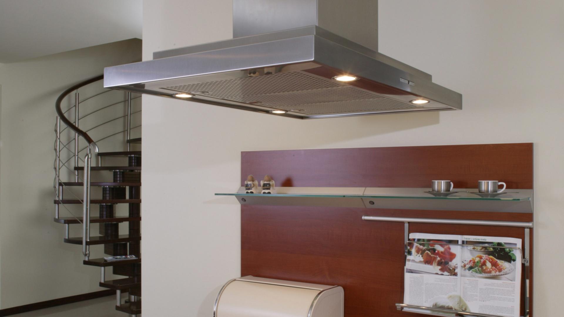 Półwysep kuchenny to sfera gotowania. Na ścianie obok, płyta meblowa z podświetlaną szklaną półką na przyprawy lub inne akcesoria, oraz wygodny uchwyt na książkę kucharską. Fot. Monika Filipiuk.