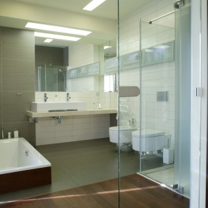 Przestronność łazienki współtworzą jasne barwy ścian i urządzeń sanitarnych, lustra i powielone w nich pasy oświetlenia sufitowego, a także szklana ściana. Fot. Monika Filipiuk.