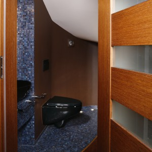 W małej toalecie, w dodatku umieszczonej pod schodami wiodącymi na piętro domu, zmieściły się tylko sedes i, dzięki zaanektowaniu na niszę fragmentu kuchni, umywalka. Fot. Bartosz Jarosz.