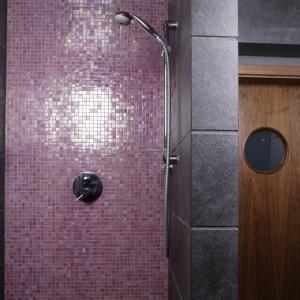 Kabina prysznicowa zajęła utworzoną w tym celu wnękę. Jej wnętrze to kompozycja różu i szarości, dla relaksu – podtynkowe dysze do hydromasażu. Fot. Bartosz Jarosz.
