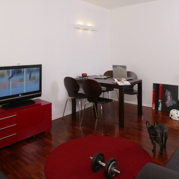 Aranżacja z czerwienią i szarościami: mieszkanie dla minimalisty