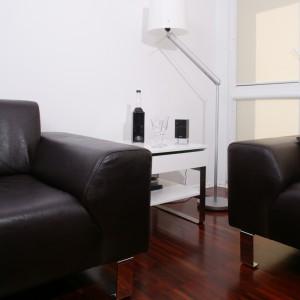 Minimalistyczna i nowoczesna aranżacja wnętrza zyskała interesujące wykończenie w postaci dwóch kanap z ciemnej skóry na chromowanych, hi-techowych, nóżkach.