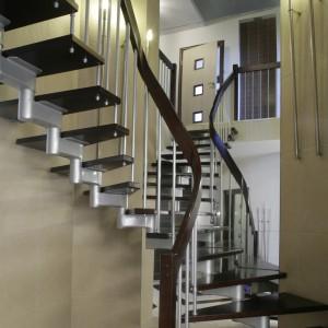 Metalowa konstrukcja z drewnianymi stopniami (wykonana na zamówienie przez firmę Perfect), odbijając się w ogromnym lustrze, robi wrażenie rozdwojenia. Drogę na górę oświetlają długie, cienkie lampy ścienne firmy Paulmann. Fot. Monika Filipiuk.