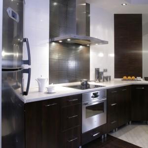 """Płytki ceramiczne o fakturze drewna orzechowego firmy Porcelanosa, """"biegnące"""" przez środek kuchni, barwą przypominają panele w użytkowych strefach mieszkania. Są jednak dużo praktyczniejsze – łatwo się czyszczą. Fot. Monika Filipiuk."""