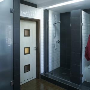 Kabina prysznicowa jest pozbawiona brodzika. Wyłożono ją jedynie czarnymi płytkami gresowymi. Podobnie wygląda gipsowo-kartonowa ścianka pomiędzy natryskiem a toaletą. Natrysk i sedes od reszty łazienki izolują szklane, przezroczyste przepierzenia. Fot. Monika Filipiuk.
