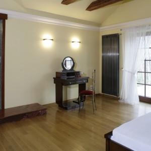 Różnicę poziomów podłogi między sypialnią i łazienką niweluje stopień z czerwonego marmuru. Klimat nostalgicznego wnętrza współtworzy nawiązująca do art déco toaletka i kute z metalu krzesło. Fot. Monika Filipiuk.