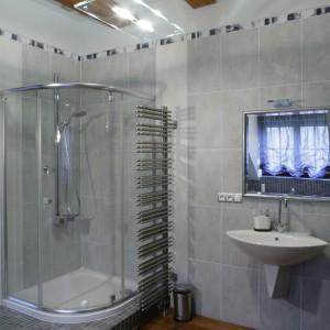 Umocowany prostopadle do ściany, tuż obok kabiny i umywalek, ażurowy grzejnik nie tylko daje przyjemne ciepło, pozwala też mieć zawsze pod ręką suchy i nagrzany ręcznik. Fot. Monika Filipiuk.