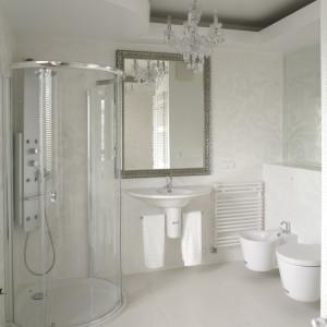 Jasny, przestronny, wykwintny – salon kąpielowy ma zwiewny, zmysłowy wystrój. Współtworzą go biel urządzeń sanitarnych, przezroczystość kabiny prysznicowej i srebrne akcenty. Fot. Bartosz Jarosz.