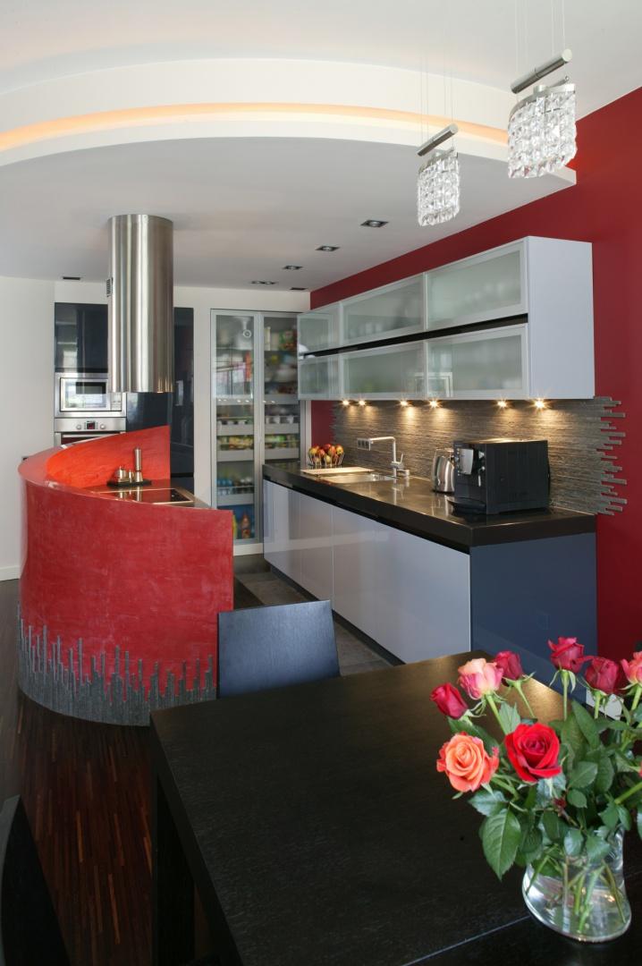 Zabudowa kuchenna została utrzymana w szaro-grafitowej kolorystyce. Pozbawione uchwytów, minimalistycznie zaprojektowane szafki, z frontami na wysoki połysk i przeszkleniami, mieszczą w sobie większość kuchennego wyposażenia. Fot. Bartosz Jarosz.