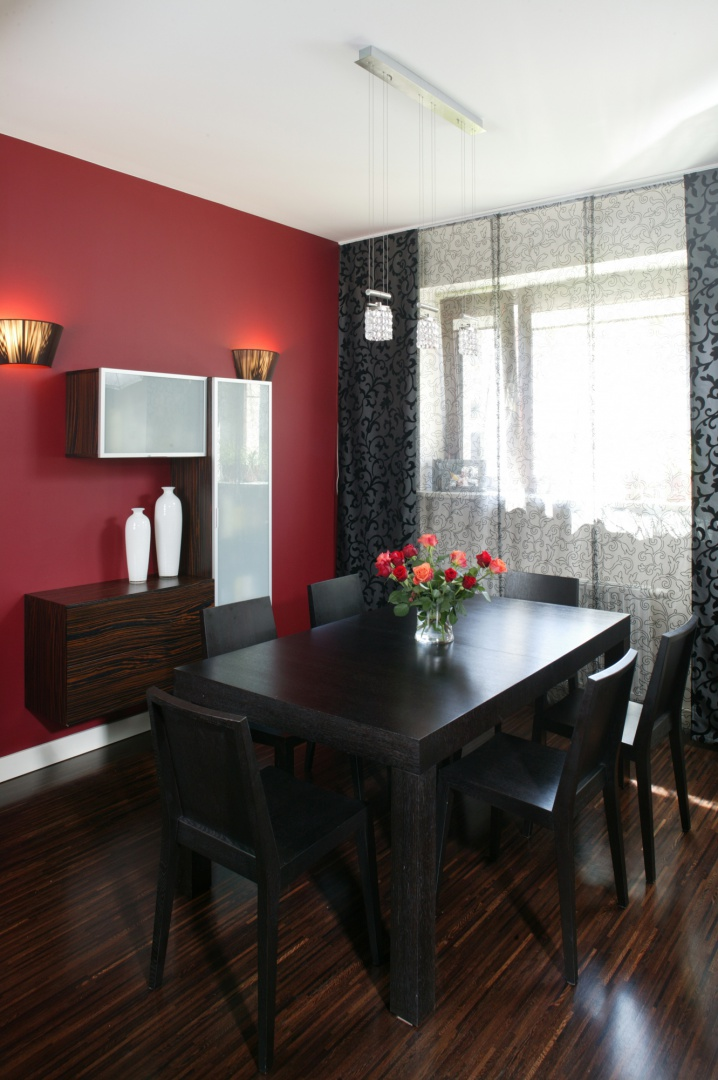 Ścianę w części jadalnianej pomalowano na ceglastoczerwony kolor. Zawieszone na niej minimalistyczne szafki, dodają jej nowoczesnego sznytu i wskazują powinowactwo z położoną tuż obok kuchnią. Fot. Bartosz Jarosz.
