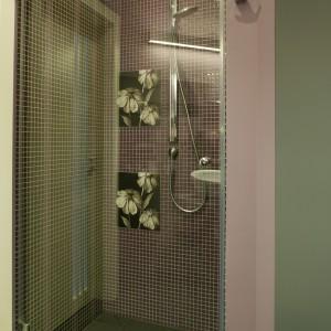 W przesłoniętej szklaną taflą kabinie prysznicowej, obok fioletowej mozaiki na ścianie (Marazzi), pojawiły się kwieciste kafle (Dado Ceramica) oraz pionowe wstawki ze szkła, wpuszczające do wnętrza dzienne światło. Fot. Bartosz Jarosz.