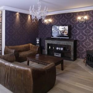 Barokowa tapeta (Finezja Studio) wyraziście odcina się od reszty wnętrza i wyznacza część gościnno-wypoczynkową, którą oświetla kryształowy żyrandol oraz kinkiety indyjskie.