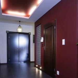 Na parterze znajduje się pomalowana na bordowo zabudowa w kształcie klocka, która zorganizowała przestrzeń dziennej strefy domu, a także posłużyła jako łazienka dla gości. Fot. Monika Filipiuk.