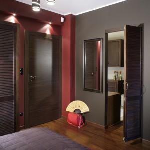 Wiśnie w czekoladzie – takie apetyczne skojarzenie wywołuje kolorystyka sypialni. Wnętrze jest jednak dosyć ciemne, dlatego dodatkowe, rozmieszczone w różnych miejscach oświetlenie było niezbędne. Fot. Monika Filipiuk.