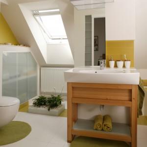 Drewniana konstrukcja-mebel, wykonana na zamówienie, stanowi podporę umywalki, ale jest jednocześnie praktyczną półką na ręczniki. Fot. Bartosz Jarosz.