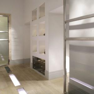 Niezwykłą dekoracją dębowej podłogi są wplecione w nią przejrzyste panele, pod którymi zostały zainstalowane lampki. Oświetlenie podkreśla fakturę drewna, nadając mu blask nowoczesności. Fot. Monika Filipiuk.