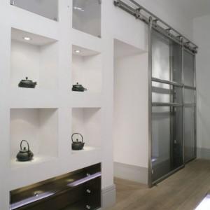 Nisze, w których można wyeksponować cenne drobiazgi, wieńczą szklane szuflady.   Nieco przepychu tej minimalistycznej konstrukcji dodają, również szklane, dekoracyjne uchwyty, sprowadzone z Anglii.