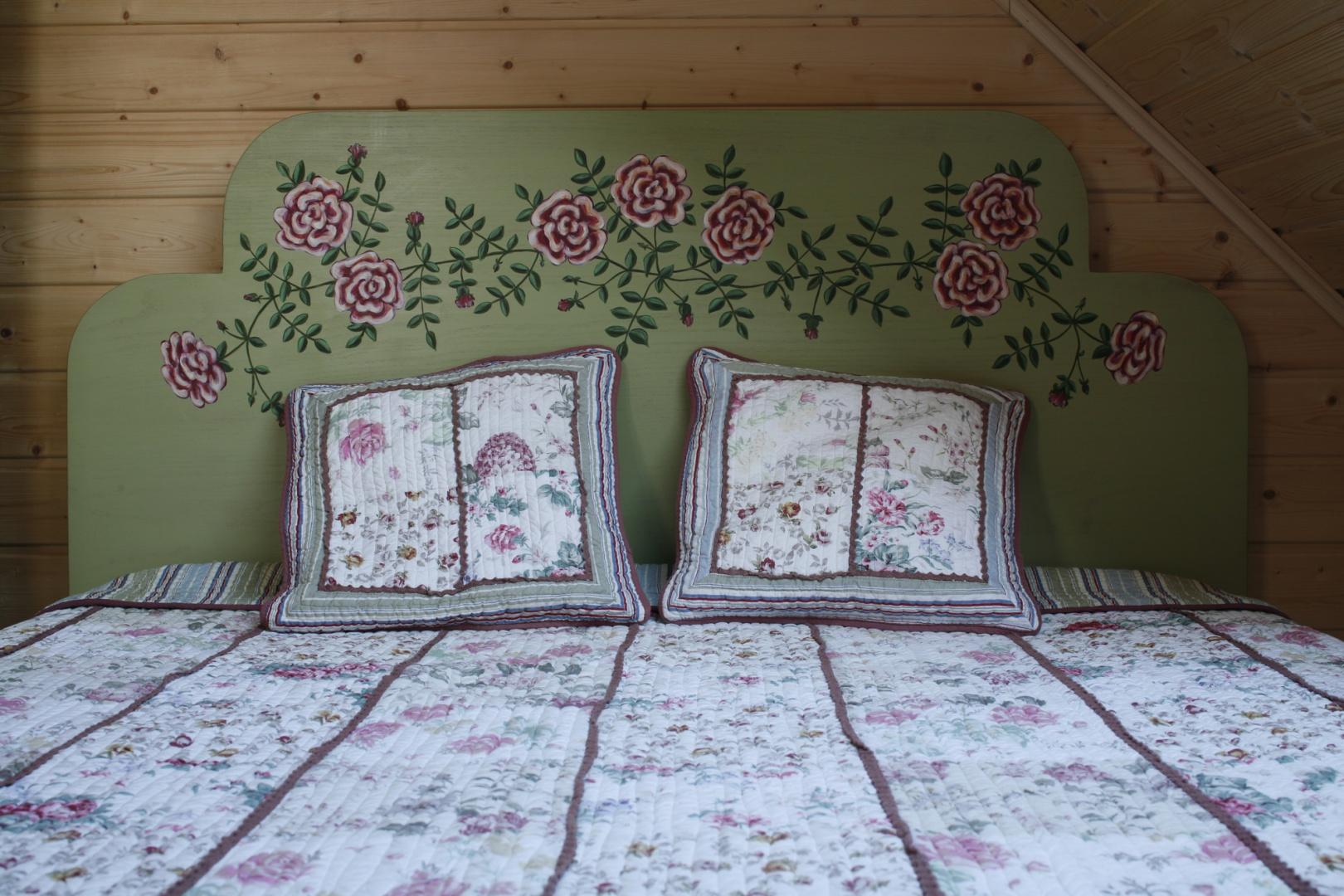 Oprócz wszechobecnego drewna i czerpanych z natury kolorów, ciepły klimat sypialni tworzą starannie dobrane naturalne tkaniny: narzuta patchworkowa, tkany ręcznie chodniczek. Fot. Bartosz Jarosz.