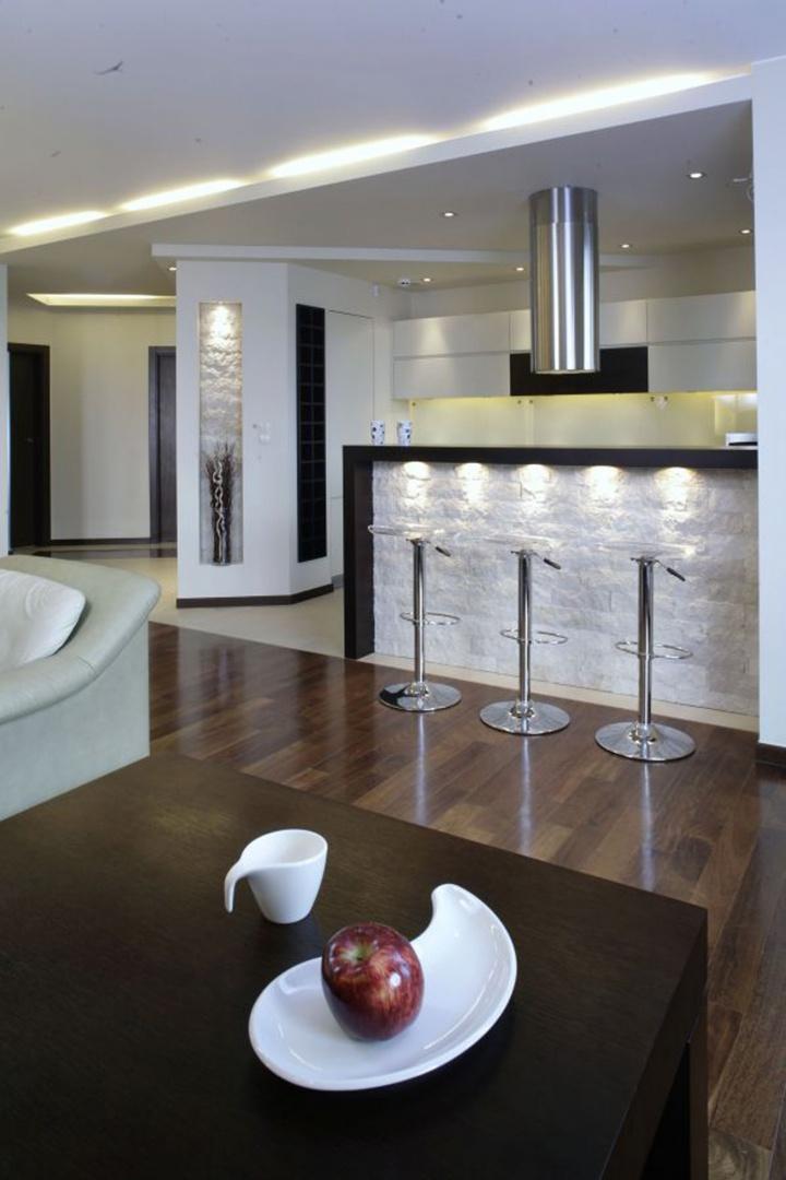 Kuchnia i salon dzielą ze sobą jedną przestrzeń. Symboliczny podział zaznacza się na podłodze. W kuchni ułożono gresowe płytki w kolorze złamanej bieli (Morfil), a w salonie drewnianą podłogę z akacji parzonej. Fot. Monika Filipiuk.
