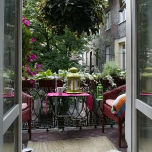 Pełen bujnej, soczystej zieleni balkon to wspaniałe miejsce na odpoczynek. Prostymi środkami (wiszący stoliczek, fotele z rattanu) zaaranżowano tu kącik, w którym można latem napić się kawy lub spokojnie przejrzeć poranną prasę. Fot. Monika Filipiuk.