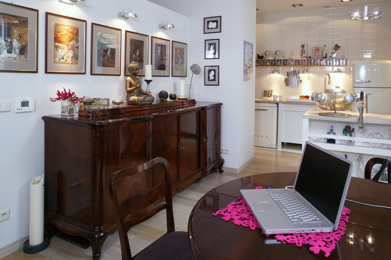 Miejsce usytuowania ściany i jej szerokość zostały dostosowane do kredensu. Kuchnia – choć efektowna – jest tłem dla urządzonego rodzinnymi pamiątkami salonu. Fot. Monika Filipiuk.