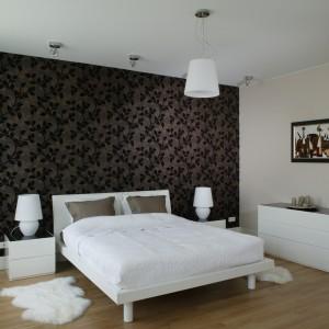Mocne akcenty kolorystyczne są w domu bardzo nieliczne, dlatego każdy z nich jest od razu zauważalny. W sypialni pojawia się w postaci brązowej tapety z dekoracyjnym, liściastym motywem. Fot. Bartosz Jarosz.