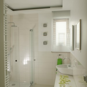 """Kremowa biel i nowoczesna klasyka – tak zaprojektowaną łazienkę łatwo """"odświeżyć"""" przy pomocy dodatków, by dostosować ją do wieku młodego lokatora. Ściany wykończono płytkami """"Tiffany Avorio"""" (prod. Fincuoghi). Fot. Bartosz Jarosz."""
