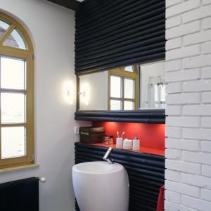 W ciemną, bambusową ścinkę za dużą, postumentową umywalką wbudowano czerwoną półkę na podręczne kosmetyki. Jest ona podświetlona niewielkimi lampkami. Fot. Monika Filipiuk.