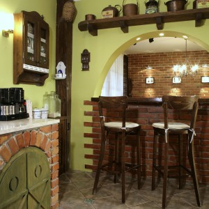 Strefę baru z drewnianym blatem i wykończoną cegłami podstawą zdobią stylowe szafki oraz półki. Otwarta przestrzeń nad barem częściowo łączy kuchnię z jadalnią. Fot. Monika Filipuk.