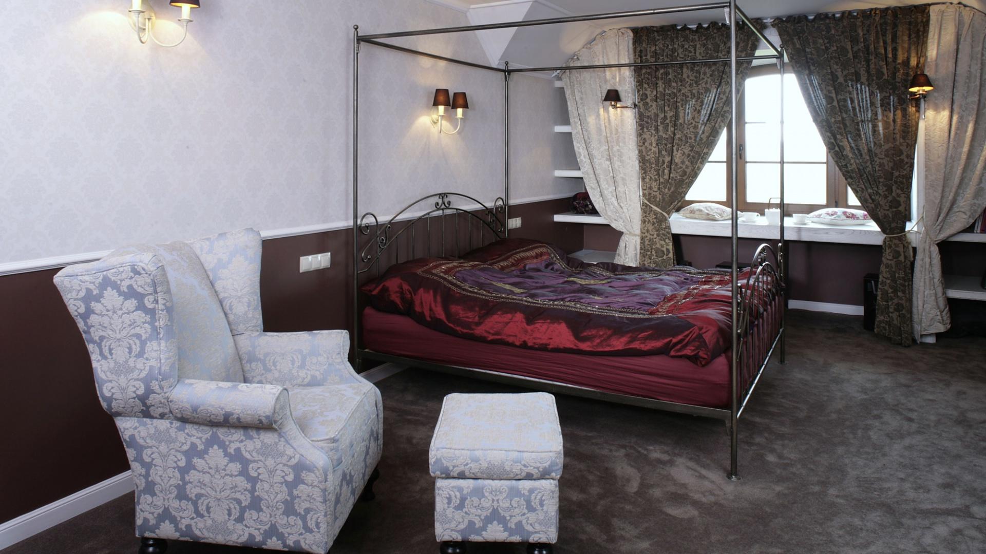"""Fotel popularnie zwany """"uszatkiem"""", w połączeniu z obszernym, małżeńskim łożem, nadaje sypialni charakter pałacowej komnaty. Czekoladowe abażury kinkietów (Darty Luz) współgrają kolorystycznie z drewnianą lamperią, dywanem i zasłonami. Fot. Monika Filipiuk."""