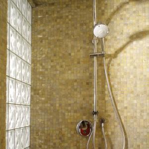 Trawertynowa mozaika (takiej samej użyto do obudowy filarku przy wannie i kącika umywalkowego), w połączeniu z luksferową ścianką, tworzą oryginalną, dużą kabinę prysznicową. Fot. Monika Filipiuk.