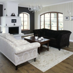 Między kanapami, na dębowej, przecieranej podłodze, położono jasny dywan, którego wzór nawiązuje do wzoru jasnej kanapy. Fot. Monika Filipiuk.