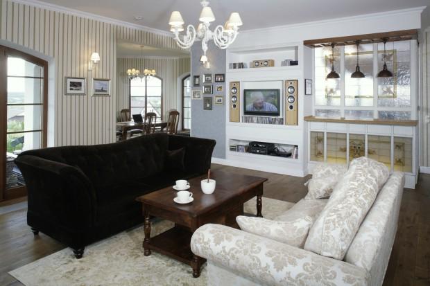 W angielskim stylu. Biała kuchnia i stylowe meble w pokoju