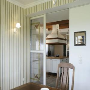 """Kuchnia z dwóch stron zamykana jest """"parawanami"""". Przesuwana ścianka, widoczna na zdjęciu, izoluje pomieszczenie od salonu. Jest jednocześnie """"przykrywką"""" dla zaaranżowanej w kącie spiżarni. Fot. Monika Filipiuk."""