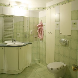 Swój delikatny kobiecy klimat łazienka zawdzięcza kolorystyce. Pastelowozielone płytki i meble w odcieniu écru tworzą ciepłą, przyjemną  dla oka kompozycję. Fot. Monika Filipiuk.