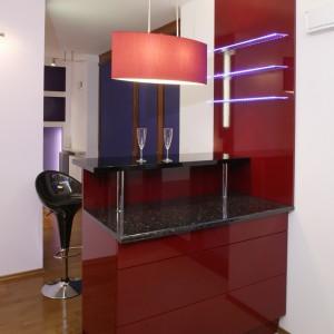 Trzy szklane półki podświetlone niebieskimi diodami, to jeden z kontrastowych, barwnych akcentów w kuchni. W zestawieniu z lśniącą powierzchnią ściany wywołują efekt świetlnej wibracji. Fot. Monika Filipiuk.