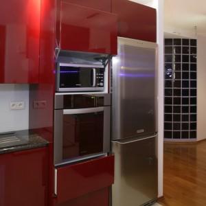 Czerwona zabudowa kuchenna ukrywa dodatkowy sprzęt AGD – nowoczesną kuchenką mikrofalową umieszczoną nad piekarnikiem, za podnoszonym do góry frontem szafki. Fot. Monika Filipiuk.