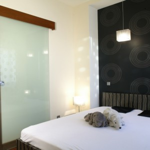 Skromnie umeblowana sypialnia (łóżko wykonane na zamówienie przez Nową Formę) nie rozprasza nastroju, który budują wzory na tapecie i zasłonach, sugerujące odniesienia do op-artu. Pozytywną energię wnoszą też lampy (Ramko). Fot. Monika Filipiuk.
