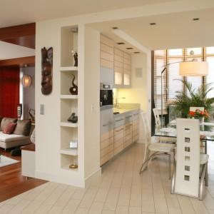 Podłogę w salonie pokrywa afrykańskie drewno doussie, ułożone na  ogrzewaniu podłogowym. W części jadalniano-kuchennej zostały ułożone płytki – na przemian matowe i polerowane. Fot. Bartosz Jarosz.