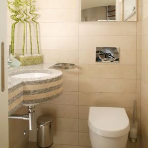 Płytki w toalecie pochodzą z oferty Iris Ceramica, ich odcień ciekawie koresponduje z zatopionymi w blacie plastrami marmuru. Fot. Bartosz Jarosz.