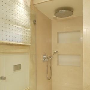 """Wnętrze kabiny prysznicowej w całości wyłożone jest płytkami gresowymi z wykończeniami z marmuru """"Crema Marfil"""". Wyposażona została w głowicę deszczową oraz natrysk ręczny. Fot. Bartosz Jarosz."""