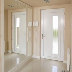 Proste, techniczne oświetlenie górne (Spotline), które zastosowano w korytarzu, pojawia się też w kuchni, dzięki czemu wnętrze jest spójne i jednolite. Fot. Bartosz Jarosz.