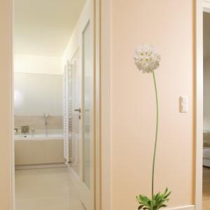 Obok sypialni małżeńskiej umiejscowiono łazienkę, do której można dostać się przez korytarz główny. Ogromny kwiat na przestrzeni między oboma pomieszczeniami przełamuje panującą w domu powściągliwość i surowość formy, dodając mu szczyptę subtelnego, kobiecego charakteru. Fot. Bartosz Jarosz.