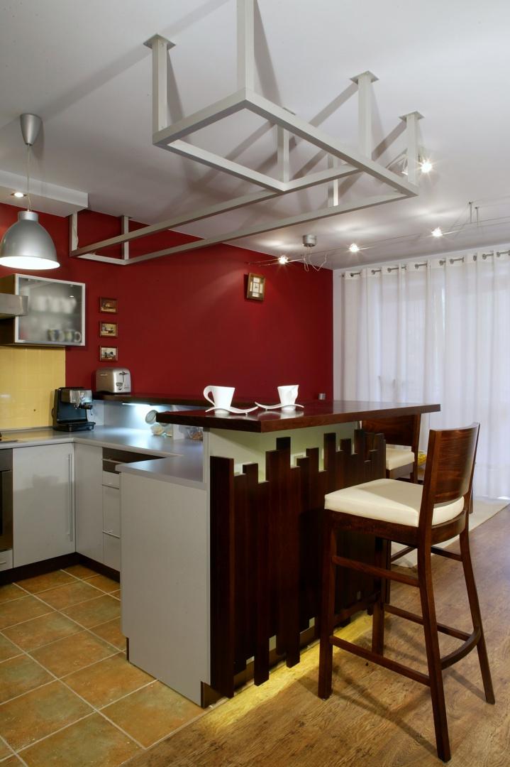 Z otwartej dziennej strefy mieszkania, kuchnię wyodrębnia podłoga z płytek gresu oraz tajemnicza konstrukcja przy suficie, odzwierciedlająca kształt zabudowy meblowej. Fot. Monika Filipiuk.