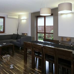 Dzienną strefę tworzą otwarte na siebie: salon, jadalnia i kuchnia. Salon i jadalnia mają wspólną podłogę - parkiet z dębu afrykańskiego. Idealnie harmonizują z nim drewniane meble. Fot. Monika Filipiuk.